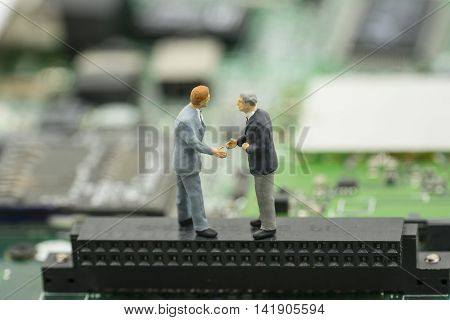 business agreement by two mini businessman shake hand on mainboard background - can use to display or montage on product