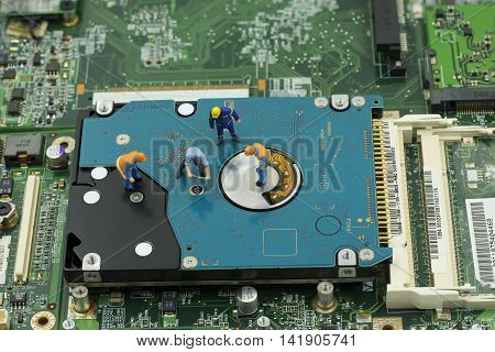 service maintainance of hard disk by mini worker team on mainboard background - can use to display or montage on products