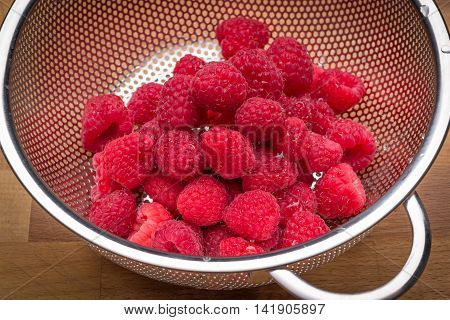 Fresh raspberries in stainless steel colander on a wood surface