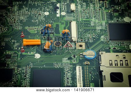 group of mini technician find out to remove a screw on mainboard and dig sign with vintage filter - can use to display or montage on products