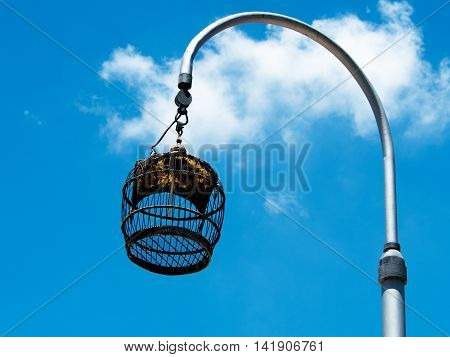 Vintage bird cage hanging on pole against with blue sky. Freedom concept.