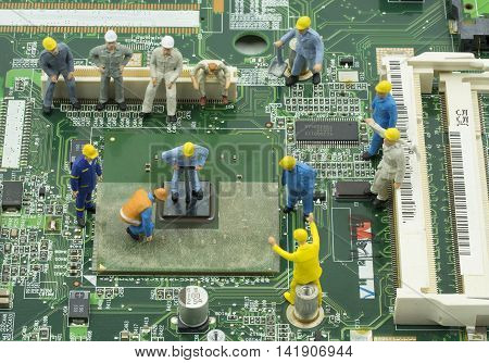 mini engineer team to repair chipset on green mainboard - can use to display or montage on product or concept of job response