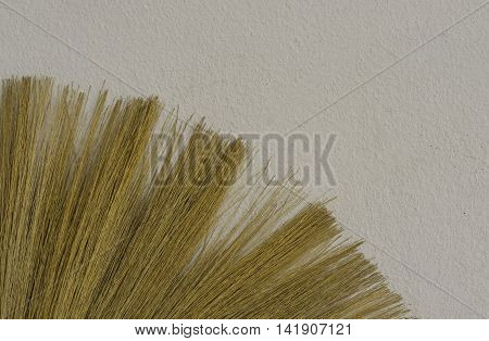 abstract brown broom stay on white cement wall - can use to display or montage on product or concept fill text on free space background