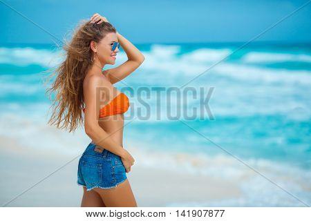 Happy young brunette woman with long blonde hair,a beautiful smile and white straight teeth, standing on the white sand of a tropical beach near the blue ocean,dressed in blue shorts and an orange bra on a bathing suit,wears blue sun glasses