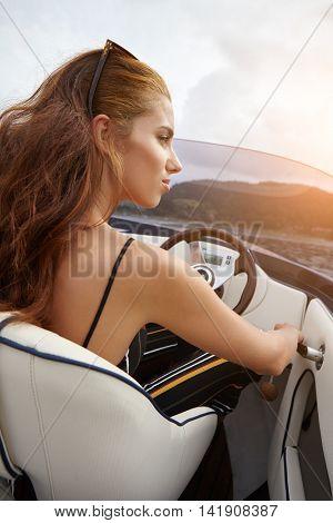 Summer vacation - young woman driving a motor boat