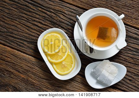Top view of cup of tea with tea bag, tea bags lemon on wooden table