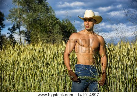 Portrait of sexy farmer or cowboy in hat looking to a side, while standing next to hay field in countryside