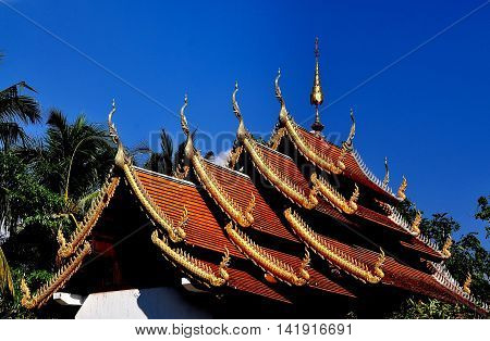 Chiang Mai Thailand - December 25 2012: Four highly pitched gabled roofs decorated with gilded dragons and chofah ornaments atop the Vihan hall at Wat Nantaran