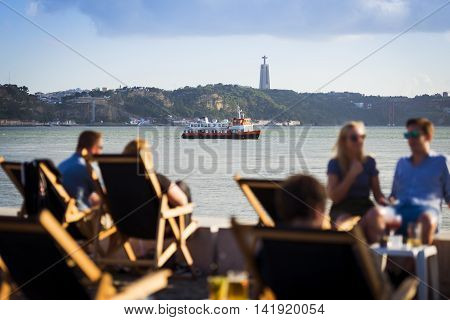 People in a esplanade in Lisbon Portugal by the Tagus River with a passenger boat (cacilheiro) crossing the Tagus River; Concept for travel in Portugal