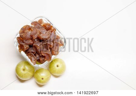 A bunch of gooseberry candies in a bowl with some gooseberries in the blurred background