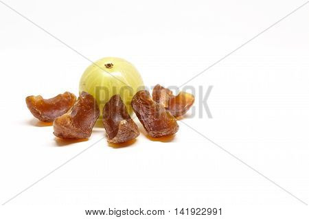 Gooseberry candies with a gooseberry in the blurred background