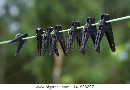 Seven black clothespegs hang on the rope