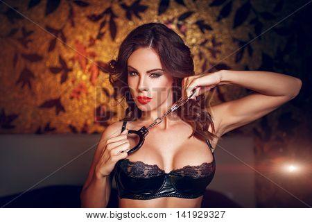 Sexy woman in black latex bra holding handcuffs in bedroom in dark at night club bdsm