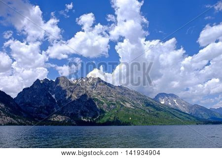 Impressive mountains with clouds by lake. Jenny lake in Grand Tetons National Park Jackson Moose Wyoming.