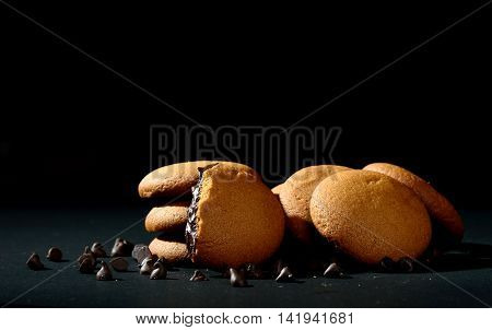 Biscuits filled with chocolate cream. Chocolate cream cookies. brown chocolate biscuits with cream filling on black background.