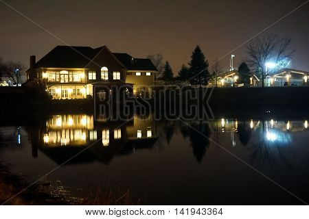 A small lake reflects the lights of the Wesmere Country Club Clubhouse during the night in December in Joliet, Illinois.