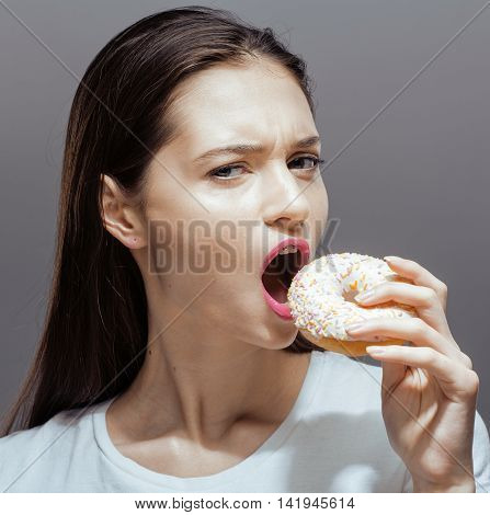 young pretty real thin girl with donut close up, unhealthy habbit bulimia concept