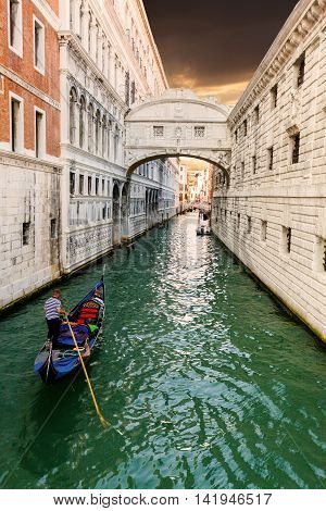 Bridge of Sighs in Venice at sunset with a floating past gondola. Travel Italy.