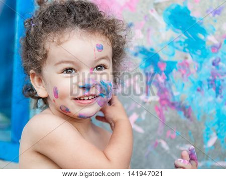 Portrait of baby girl are coloring her own face by paints