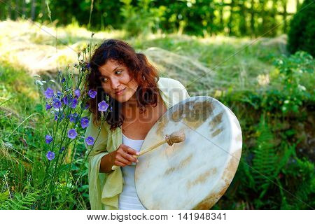 beautiful shamanic girl with shaman frame drum on background with leaves and flowers