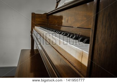 A classical looking dark stained, wooden upright piano.