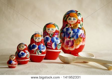 Row Russian Matryoshkas and two wooden spoons.