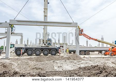 Mobile crane is operating and worker is assembly concrete joist in high place. Height worker is placing truss on building skeleton.