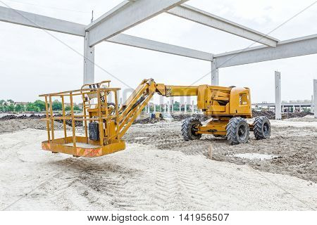 Cherry picker is parked below concrete skeleton of new assembled building frame.
