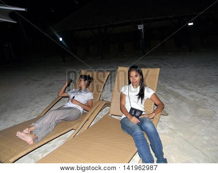 LAPU LAPU, CEBU / PHILIPPINES - JULY 28, 2011: Women relax in lounge chairs during the night at the beach of Shangri-La's Mactan Resort and Spa.