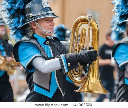 Teen baritone player marching in the band.