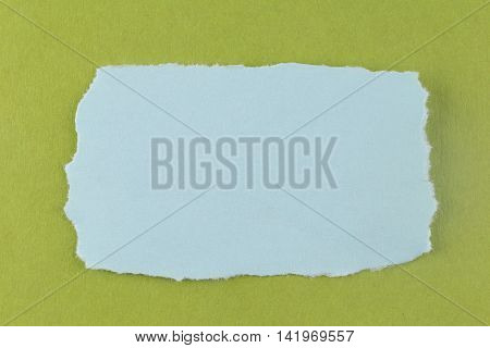 Blue paper tear on green cardboard background and you can input text in copy space.