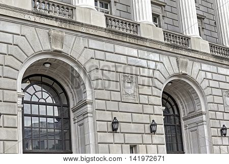 Front of Internal Revenue Service Building in Washington DC showing slogan engraved on building by Oliver Wendall Holmes that says Taxes are what we pay for a civilized society.