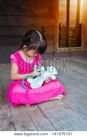 Adorable Asian Girl Playing Doctor Or Nurse With Plush Toy Bear At Home.
