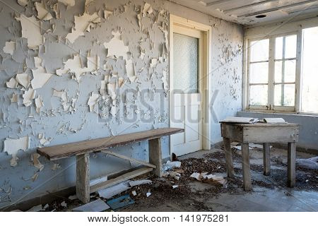Interior of a dirty an empty demolished abandoned room with open windows an dirt on the floor