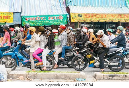Saigon, Vietnam - October 13, 2013; Scores of motorcycles stopped in street many with rider and passenger one with three wearing pollution masks as typical in Asian cities.