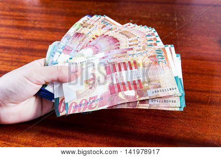 A female hand holding two hundred shekel bank notes against wood background. Concept photo of money banking currency and foreign exchange rates. poster
