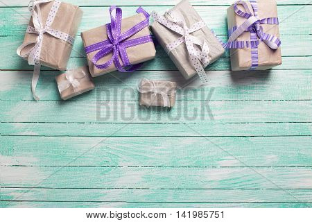 Many festive gift boxes with presents on turqoise wooden background. Selective focus. Place for text. Toned image.