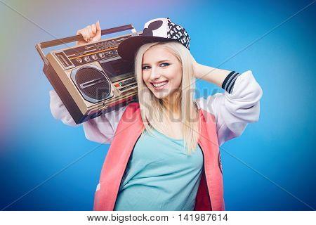 Smiling female teenager holding retro boom box on blue background