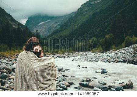 Man and woman wrapped in warm blanket outdoor, hiking in mountains, bad cold weather with fog