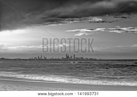 The skyline of the Gold Coast City seen from a beach in Coolangatta Queensland Australia. The evening sun casts long shadows over the waves.