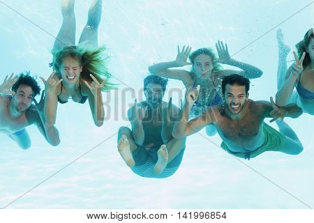 Group of young friends having fun underwater in swimming pool