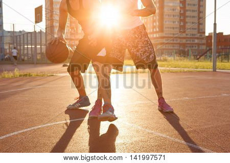 Two guy play basketball at district sports ground against a backdrop of high-rise residential buildings. Backlight. The legs and hands of players without faces.
