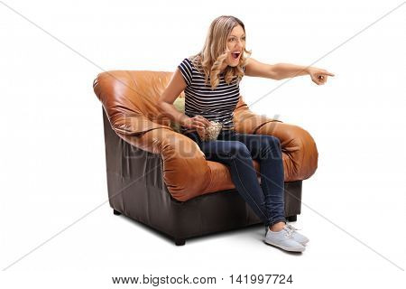 Laughing young woman watching something hilarious on TV and having some popcorn isolated on white background