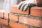 Close up of industrial bricklayer installing bricks on construction site poster