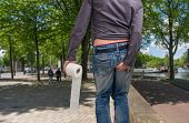 Man holding toilet paper roll and holding his butt on the street. Diarrhea concept. poster
