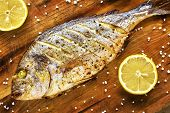 Roasted gilt head bream fish on a wooden table with lemons and coarse grained salt. poster
