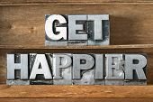 get happier phrase made from metallic letterpress type on wooden tray poster