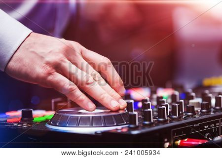 Closeup Hands Of Disk Jockey At The Dj Controller Wearing In White Shirt At Night Club. Edm, Party C