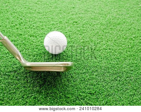 Golf Ball And Iron Golf Club In Driving Range With Copy Space