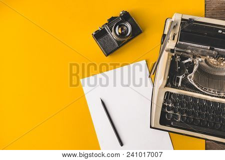 Typewriter, Vintage Film Camera, Sheet Of Paper And Pencil On A Yellow Background, Top View. Creativ